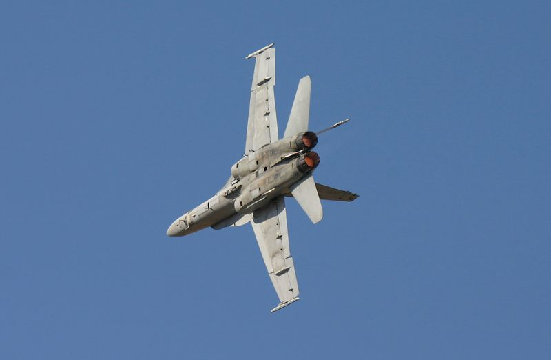 FA-18 Hornet in a hard right bank in full after burner.
