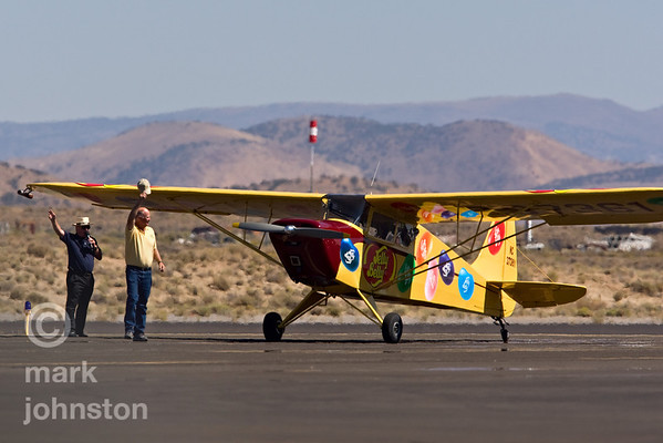 """Kent Pietsch greets the crowd after a power-off """"dead stick"""" aerobatic routine in his 1942 Interstate Cadet that starts from an altitude of 6,000 feet and ends with Kent landing at show center, during the 2007 National Championship Air Races and Air Show in Reno, Nevada, USA."""