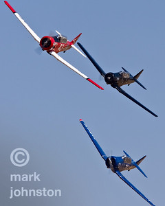 """Close racing action is what makes the T-6 Class at Reno a fan favorite.  Here, Race 75 """"Warlock"""", flown by Al Goss [lower right], Race 6 """"Six Cat"""", flown by Nick Macy, and Race 43 """"Midnight Miss III"""", flown by Dennis Buehn, compete during the 2007 National Championship Air Races in Reno, Nevada."""