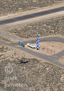 """A T-6 Class aircraft passes the """"Home Pylon"""" that marks the finish line of the race course during a practice race at the Pylon Racing Seminar.  The National Championship Air Races and Air Show feature several classes of up to laps aircraft racing together for up to eight laps around a closed course demarcated by specially marked poles [pylons] at speeds exceeding 500 mph.  The Reno Air Racing Association sponsors the Pylon Racing Seminar as a unique and productive opportunity for race pilots to prepare, practice, and become certified to race in the National Championship Air Races.  The Pylon Racing Seminar is held at Nevada's Reno Stead Field during the month of June."""