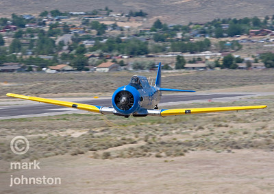 "A T-6 Class aircraft approaches the ""Home Pylon"" during a practice race.  The National Championship Air Races and Air Show feature several classes of up to laps aircraft racing together for up to eight laps around a closed course demarcated by specially marked poles [pylons] at speeds exceeding 500 mph.  The Reno Air Racing Association sponsors the Pylon Racing Seminar as a unique and productive opportunity for race pilots to prepare, practice, and become certified to race in the National Championship Air Races.  The Pylon Racing Seminar is held at Nevada's Reno Stead Field during the month of June."