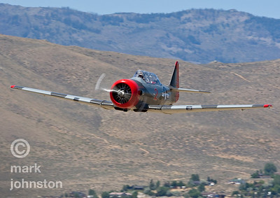 "A T-6 Class racer approaches the ""Home Pylon"" during a practice flight.  The National Championship Air Races and Air Show feature several classes of up to laps aircraft racing together for up to eight laps around a closed course demarcated by specially marked poles [pylons] at speeds exceeding 500 mph.  The Reno Air Racing Association sponsors the Pylon Racing Seminar as a unique and productive opportunity for race pilots to prepare, practice, and become certified to race in the National Championship Air Races.  The Pylon Racing Seminar is held at Nevada's Reno Stead Field during the month of June."