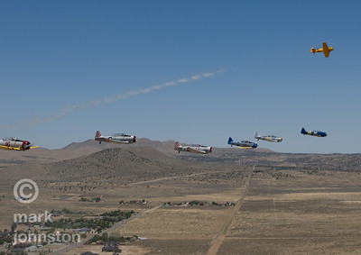 As the pace plane pulls up and away, a flight of T-6 Class aircraft descends onto the race course during the National Championship Air Races & Air Show, held each year near Reno, Nevada, USA.