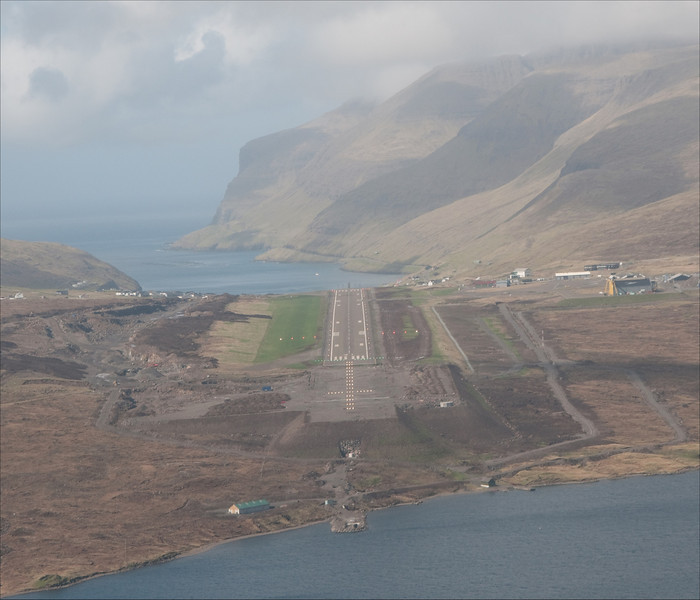 RW 31 approach into the Faroe islands LOC DME NDB in G-OOJP. This is a tricky place. Just to the left of the shot is a ridge that is at right angles to the brisk atlantic winds. The ocean surface beyond the runway is a couple of hundred feet down. The effect is that you can encounter downdrafts of 2000' a minute after take-off and more if the conditions are right.