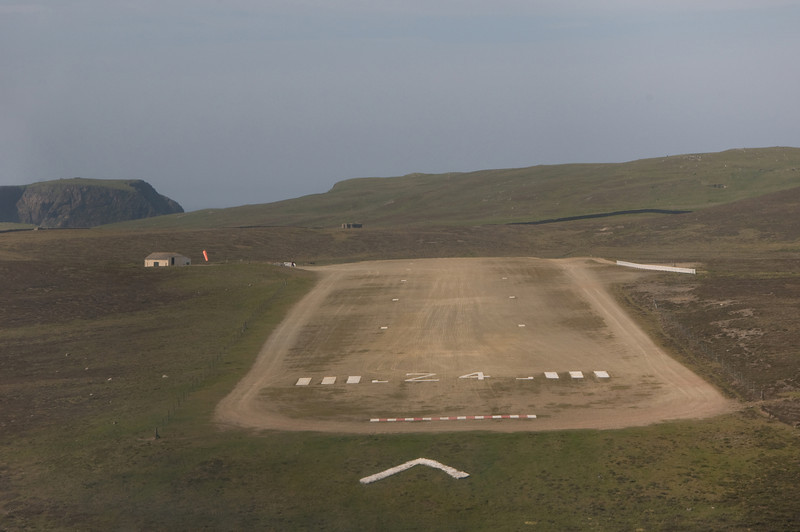 G-OOJP crossing the threshold at Fair Isle. The surrounding terrain is steep and it can be turbulent. The main hazard appears to be large seabirds that rise and swoop beneath you. That hill in the back ground rises quite steeply. The chevron painted on the grass is nearly vertical.
