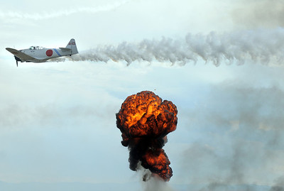 A World War II Japanese Zero flies near a fiery blast simulating explosions during Tora Tora Tora re-enacment of the bombing of Pearl Harbor at Saturday's Rocky Mountain Airshow at Rocky Mountain Metropolitan Airport. August 27, 2011 staff photo/ David R. Jennings