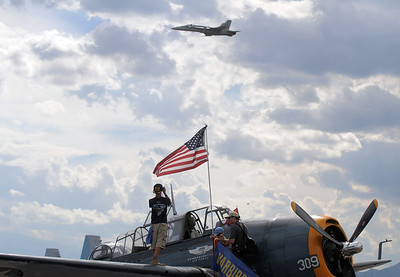 A volunteer on the wing of a World War II TBM-3E airplane watches a U.S. Navy F-18 perform during Saturday's Rocky Mountain Airshow at Rocky Mountain Metropolitan Airport. August 27, 2011 staff photo/ David R. Jennings