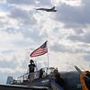 A volunteer on the wing of a World War II TBM-3E airplane watches a U.S. Navy F-18 perform during Saturday's Rocky Mountain Airshow at Rocky Mountain Metropolitan Airport.<br /> August 27, 2011<br /> staff photo/ David R. Jennings