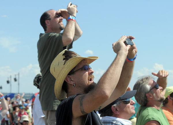 Dennis McAdd, front, from Broomfield,  and Lyle Maretech, from Parker, take pictres of a U.S. Airforce B-2  bomber as it flies over the airport during Saturday's Rocky Mountain Airshow at Rocky Mountain Metropolitan Airport.<br /> August 27, 2011<br /> staff photo/ David R. Jennings
