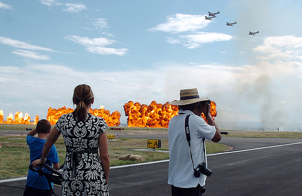 Rocky Mountain Airshow fans watch balls of flames go up while World War II Japanese aircraft fly by during a Commemorative Air Force, Peral Harbor reenactment during Saturday's at Rocky Mountain Metropolitan Airport.<br /> August 27, 2011<br /> staff photo/ David R. Jennings