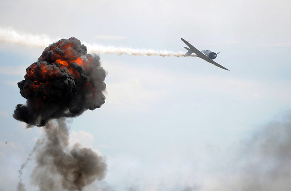 A Japanese World War II airplane flies past an explosion simulating the attack at Perl Harbor during Saturday's Rocky Mountain Airshow at Rocky Mountain Metropolitan Airport.<br /> August 27, 2011<br /> staff photo/ David R. Jennings