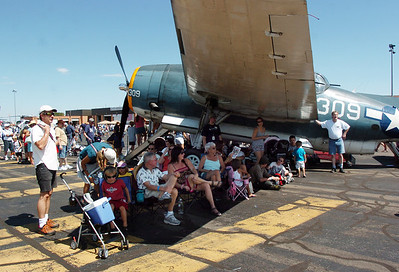 Airshow fans watch the aircraft perfomances in the shade of an airplane during Saturday's Rocky Mountain Airshow at Rocky Mountain Metropolitan Airport. August 27, 2011 staff photo/ David R. Jennings