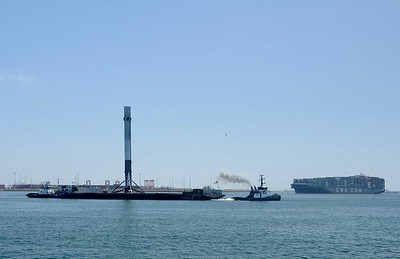 Here comes the rocket on the barge towed up from the coast of Mexico followed by big container boat