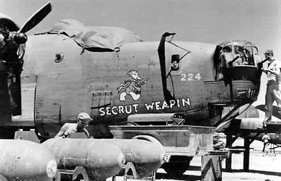 Port side of Secrut Weapin  taken on Kwajalein Island with the ground crew loading 1,000 lb bombs. Unknown year.