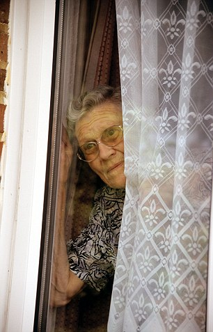 elderly lady looking out of window concerned