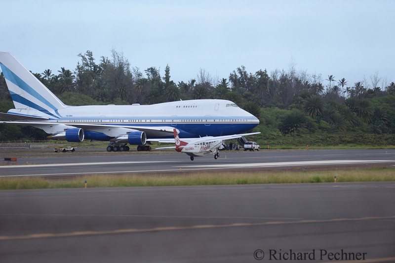 Mokulele's Flight #2014 from Kona landing at Kahului Airport in front of the 747SP-21 parked on the outer edge of the airport.