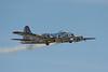 Boeing B-17 flies past with engine smoking.