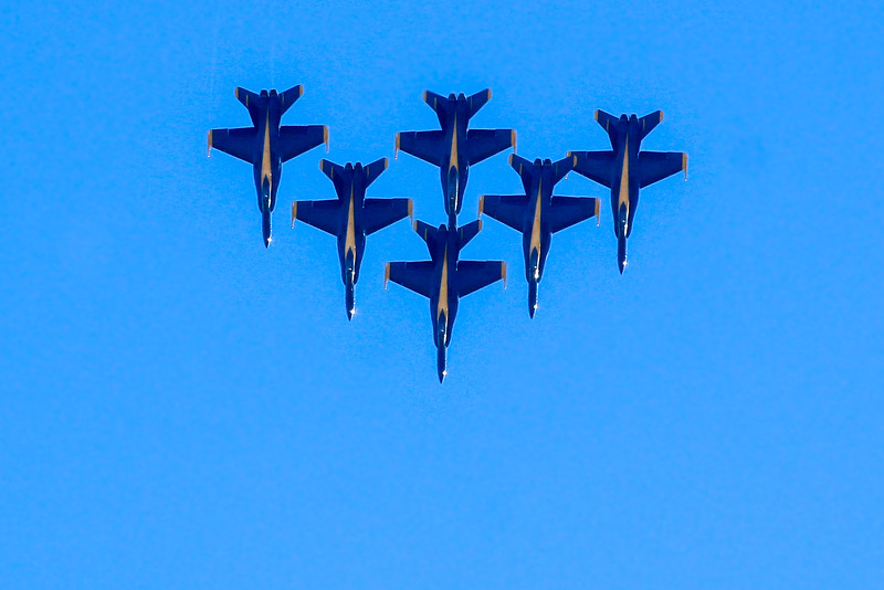 All 6 Blue Angels complete a loop in tight formation at far end of field.