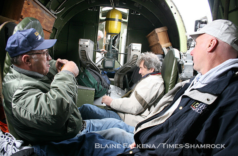 BLAINE FALKENA/Staff Photographer<br /> Richard Smith, left, takes a picture of Ron Marchetti, center, as WNEP chief photographer Paul Kielbasa looks on Wednesday during takeoff from Binghamton, New York on the way to Hazleton Municipal Airport in a B-17 Flying Fortress.