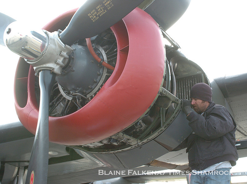 BLAINE FALEKNA/Staff Photographer<br /> Jeremy Cain of the Collings Foundation replaces an intake tube on an engine of the B-24 Liberator Wednesday morning in Binghamton, New York.