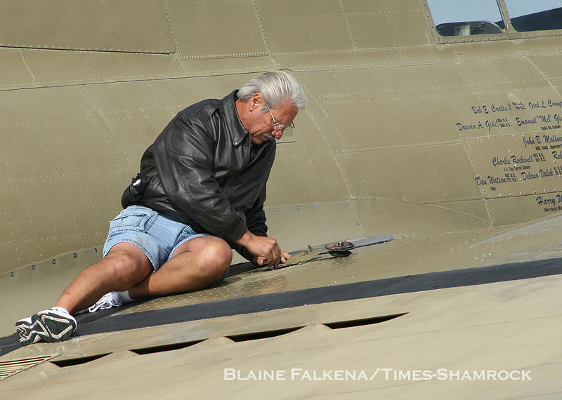 BLAINE FALKENA/Staff Photographer<br /> B-17 Flying Fortress pilot Mac McCauley puts a stick into the fuel tank to double check the amount of fuel before flight Wednesday morning.