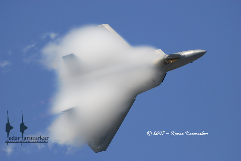 Vapor all over its fuselage, the F-22A Raptor makes a Pass.