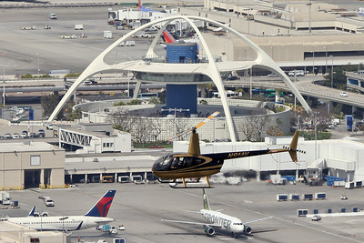 Star Helicopters Robinson R-44, N91AV, over the Theme Building at LAX