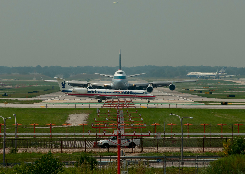 a 747 landing on runway 9R at O'Hare International Airport comes close to a American Airlines Regional Jet after it landed on 4R.
