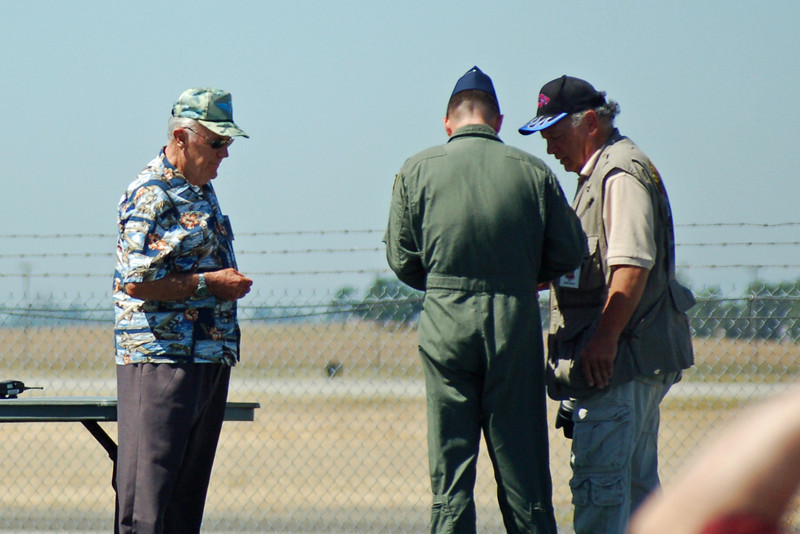 That's retired general and all around Mr. Brass @#$@!, Chuck Yeager, at the left of the pic in the Hawaiian shirt. He was supposed to fly the legacy flight that day but didn't due to a wrist injury.