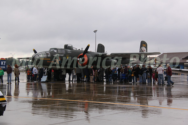 Burlington Air Show 2010 / Fly Iowa 100<br /> Some of the crowd took refuge under the wing of a B25 during the rain.