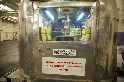 """USS Hornet Museum. Mobile Quarantine Facility – Apollo 14 astronauts Mitchell, Shepard, and Roosa were quarantined in this trailer to protect the Earth from potential """"moon germs"""" while they were being transported back to the space center following their splashdown."""