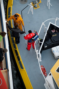 The pilot steps through a side hatch in the cruise ship on the deck of the pilot boat.