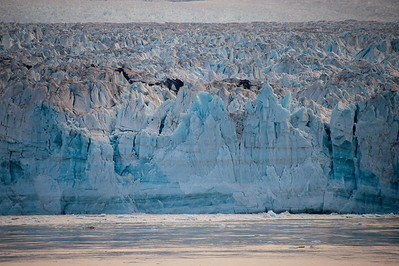 The blue color is caused by the dense ice absorbing the longer wavelengths of visible light.