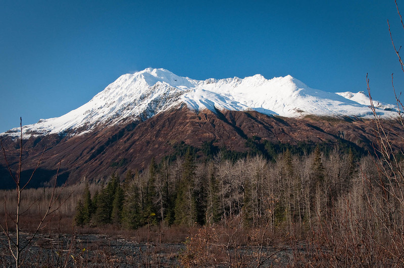 Part of the Chugach Mountain Range, located in Seward, Alaska.  Photo taken in late October after the first snow.  The winds were brisk on this particular day - you can see the snow kicking up on the summit.