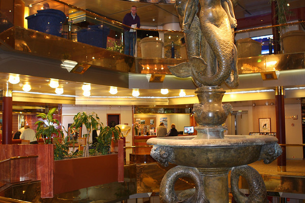 Deck 7, the Upper Promenade Deck shows the front desk and the shore excursions desk.