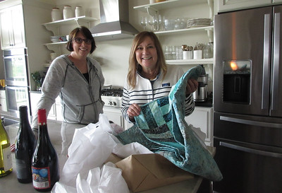 Sandra and Barbara, , in their Barefoot Contessa-inspired kitchen, opening a lap quilt Susie made for them.