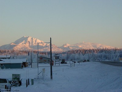 "Winter view of Mt. Drum (on the left) and Mt. Wrangell (with a puff of steam from the fumaroles on top) over ""downtown"" Glennallen."