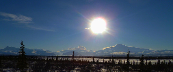 February 14, 2011:  Taken from around Mile 16 on the Nabesna Rd, looking across miles of swampy tundra, the sun shines down on Mt Sanford (right of center), Black Mt (just to left of center, split by a small black spruce) and Tanada Ridge (peak at far left) with Mt Wrangell under the clouds in the background.