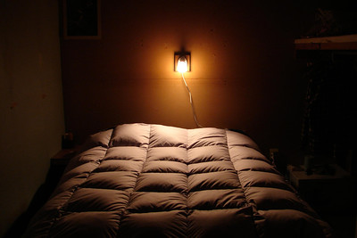 A down comforter and a reading light.  What more could one want in a bedroom?  Well... when alone, anyway.  This is the old bedroom, now history, with a new one that offers more room, better lighting, and is nicer looking using some of the same space.