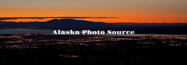 Alaska. View from Glen Alps of sunset over big city lights of Anchorage, with Cook Inlet and Mt. Susitna in background.