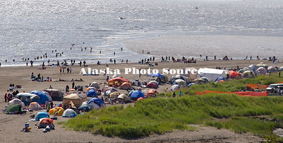 Alaska. A colorfull view of salmon dipnetters at the mouth of the Kenai River, with thier cluster of camping tents in the foreground.