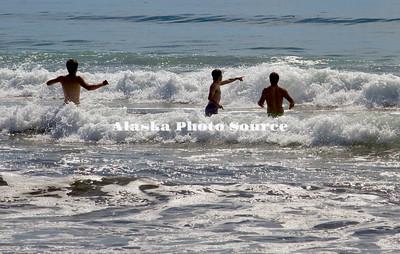 Alaska, Summer view of boys swimming at Narrow Cape Beach, along Pasagshak Bay Road, Kodiak.