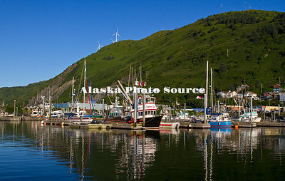 Alaska, Scenic view of boats in St Paul Harbor, with wind turbines on the emerald mountainside.