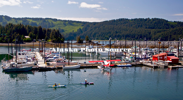 Alaska. Summer view of Seldovia small boat harbor with boys kayaking.