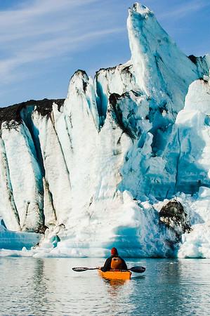 Kayaking by 'kryptonite' like iceberg at Bear Glacier, Kenai Fjords National Park, Alaska
