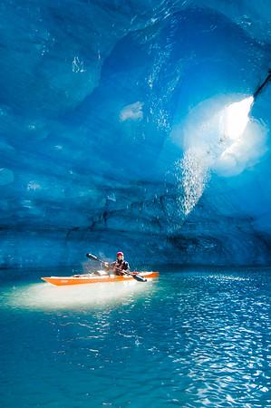 Kayaker paddles in beam of light and water melting from inside an iceberg cavern at Bear Lake, Kenai Fjords National Park, Alaska