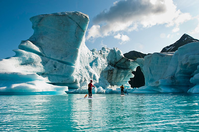 Two adults on stand up paddle board (SUP) observe hole melted in iceberg on Bear Lake in Kenai Fjords National Park, Alaska.