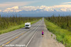 Female tourist taking pictures of traffic on the scenic Glenn Highway near Glennallen with Mt. Drum and the Wrangell Mountains in the background, Southcentral Alaska.<br /> <br /> July 05, 2014