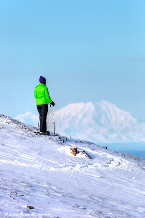 Woman snowshoer taking in the view of Mt. Foraker from Blueberry Hill at the Glen Alps area of Chugach State Park, Anchorage, Alaska<br /> <br /> February 18, 2013
