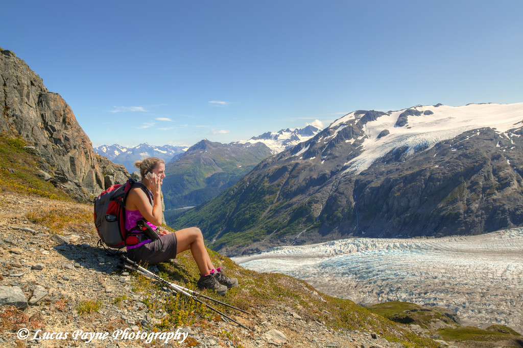 Female hiker taking a break and talking on a cell phone next to Exit Glacier in the Harding Icefield near Seward, Kenai Fjords National Park, Kenai Peninsula, Southcentral Alaska. <br /> <br /> August 02, 2014